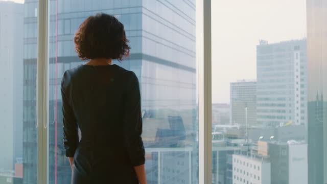 Following Shot of the Successful Businesswoman in a Striking Black Dress Walking Through Her Office and Looking out of the Window Thoughtfully. Modern Business Office with Personal Computer and Big City View.