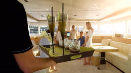 Following Shot of the Waiter Walking with a Tray Full of Exotic Cocktails, Serving them to a Company of Young People on a Yacht.