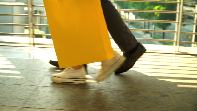 following side view: foot of businessman and chinese girlfriend walking together after they having shopping together - shopping bag stock videos & royalty-free footage