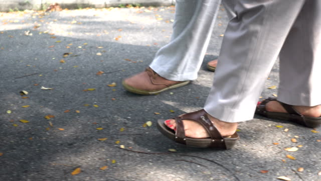 following side view: foot of senior husband walking besides wife in park