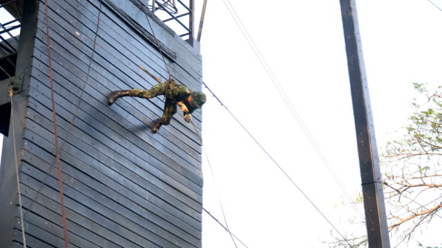following: soldier training rappel with rope by walk down. military man does hanging on climbing equipment - abseiling stock videos & royalty-free footage
