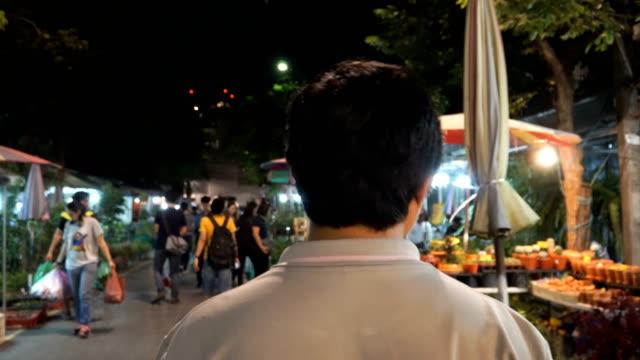 following Thai guy at a tree night market in Bangkok