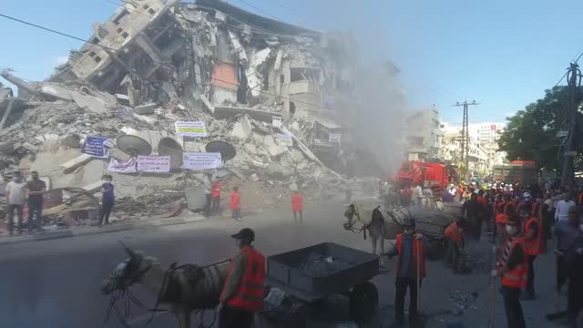 following the destructive attacks of israel in the blockaded gaza strip, residents of the city have all begun to clear the debris of the destroyed... - striscia di gaza video stock e b–roll