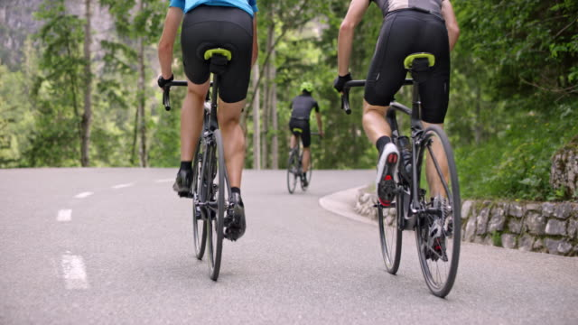slo mo following three male cyclists riding their road bikes up a mountain road - bicycle trail outdoor sports stock videos & royalty-free footage