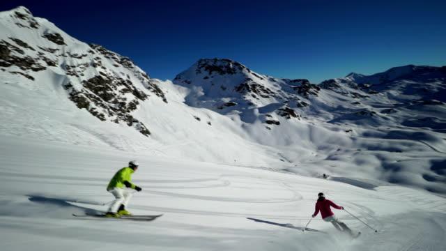 following to skiers carving in wonderful skiing region