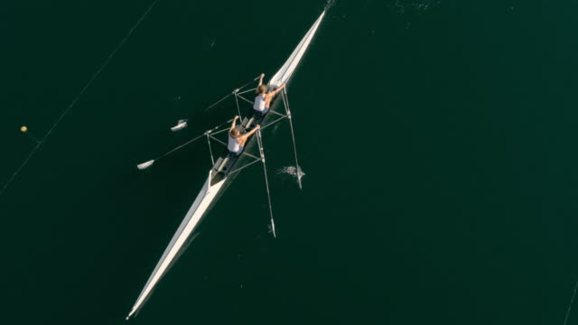 aerial following two athletes rowing across a lake in a double scull - rowing stock videos & royalty-free footage