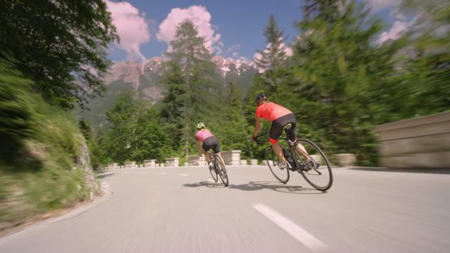 följande två kvinnliga road cyklister fallande berget på en pittoresk bergsväg - landsväg bildbanksvideor och videomaterial från bakom kulisserna