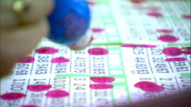 vídeos y material grabado en eventos de stock de following unidentifiable female hand using red dauber marker to mark numbers on bingo card as they are called game gamble gambler gambling lottery... - bingo