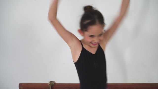 アジアの10代のバレエダンサーが練習し、晴れた日にスタジオクラスでバレエジェスチャーを学び、位置の感情と笑顔で学ぶ様子を見てください。 休憩中にフリースタイルを示す女の子。毎� - one teenage girl only点の映像素材/bロール