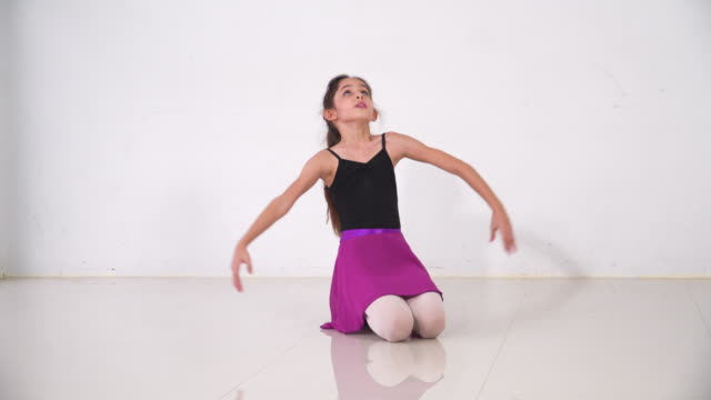 アジアの10代のバレエダンサーの練習を続け、晴れた日にスタジオクラスでバレエジェスチャーを学び、笑顔で笑顔でフルセットを見せる。週末のアクティビティでの毎日の子供のレジャー� - one teenage girl only点の映像素材/bロール