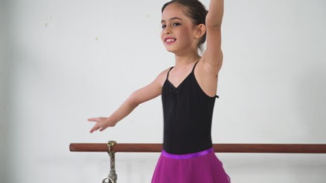 アジアの10代のバレエダンサーが練習し、晴れた日にスタジオクラスでバレエジェスチャーを学び、位置の感情と笑顔で学ぶ様子を見てください。週末のアクティビティでの毎日の子供のレ� - one teenage girl only点の映像素材/bロール