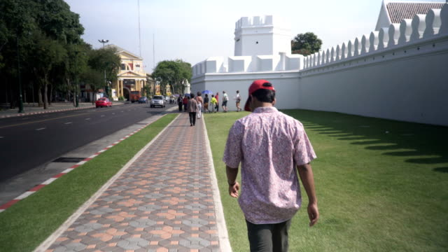 following view: young traveler walking on the street  beside wat phra kaeo in bangkok - temple body part stock videos and b-roll footage