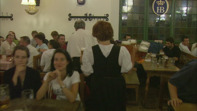 POV Following waitress serving beer in Hofbrauhaus, Munich, Bavaria, Germany