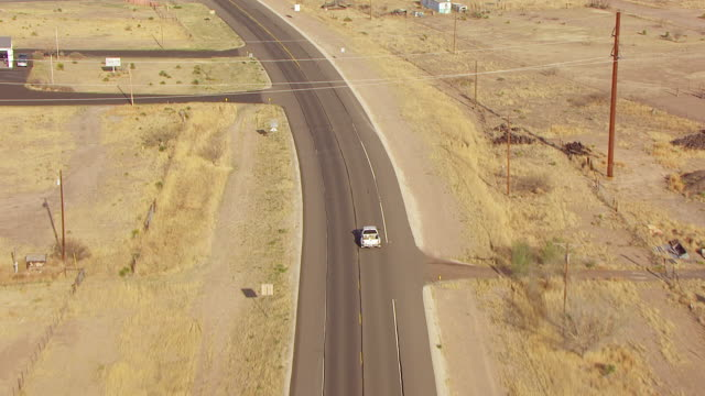 WS AERIAL TU Following white truck driving on road and town in Chihuahuan Desert / Marfa, Texas, United States