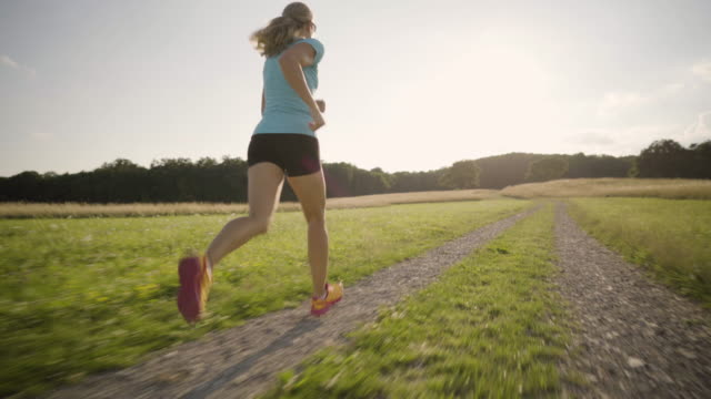 4K following woman jogging in rural landscape on sunny afternoon