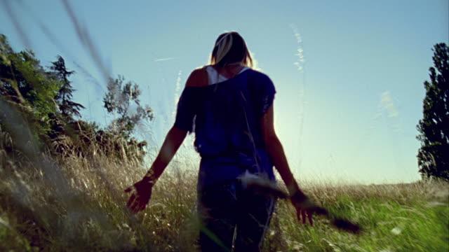 POV, MS, Following young woman walking through grass in meadow, rear view, Saint Ferme, Gironde, France