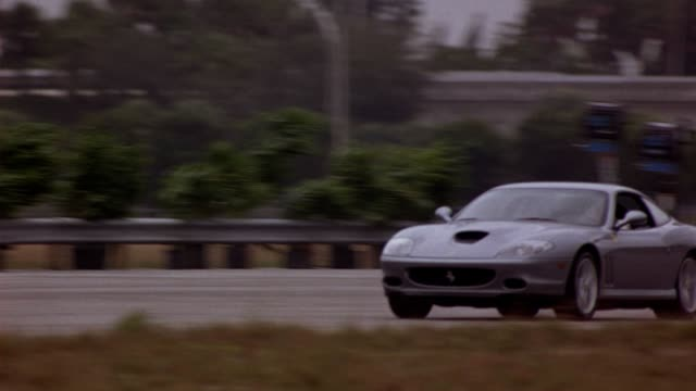 Following-pan of a silver Ferrari accelerating by the stunt-crew, crash-car, and crane.