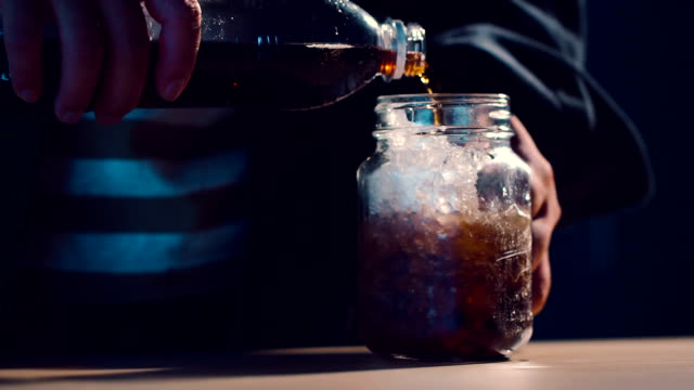 Food and Drink Cinemagraphs : Hipster man pouring cola soda into glass of ice