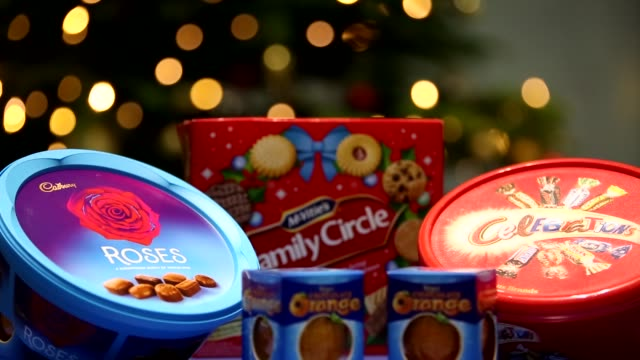 gvs of christmas chocolates and biscuits; england: london: int close shots of cadburys roses tub, celebrations tub, family circle biscuits selection,... - chocolate stock videos & royalty-free footage