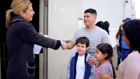 vídeos y material grabado en eventos de stock de banco de alimentos en voluntarios saludo familia hispana mientras en línea de las donaciones - voluntario