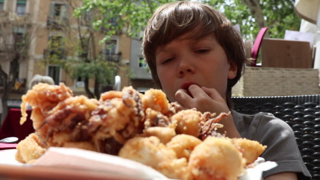 vídeos de stock e filmes b-roll de food, battered deep-fried calamari child eat - marisco