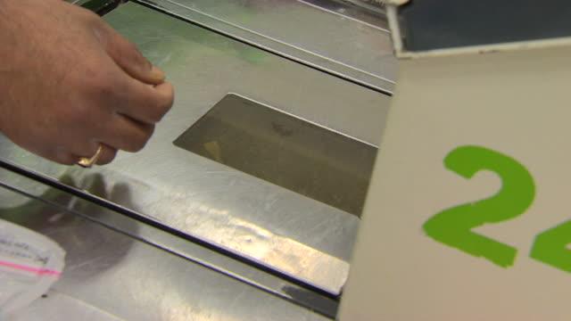 vídeos de stock e filmes b-roll de food being passed through checkout at asda supermarket - cadeia de lojas