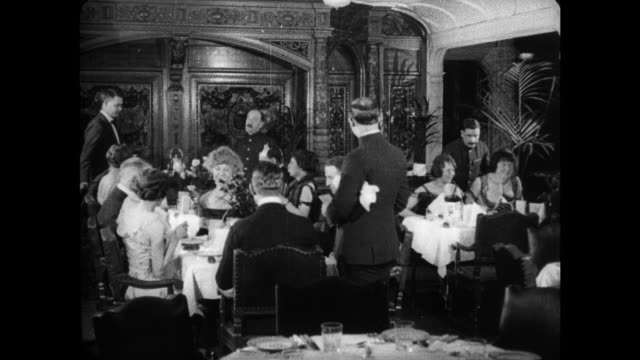 Food being plated in a service area and carried out by waiters / passengers in formalwear being seated in the ornate dining room eating dinner The...