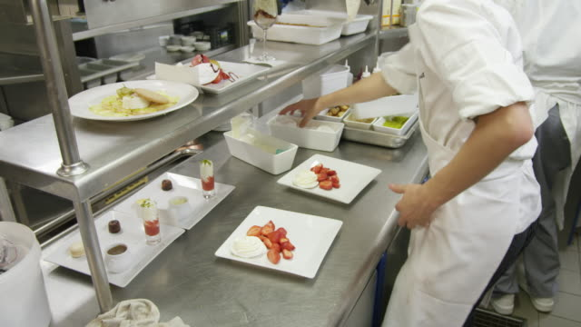 POV food being prepared at the cold plating area in a restaurant kitchen