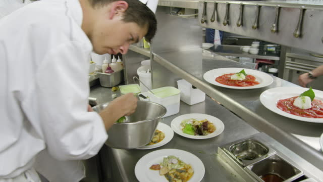 POV food being prepared at the hot plating area in a restaurant kitchen