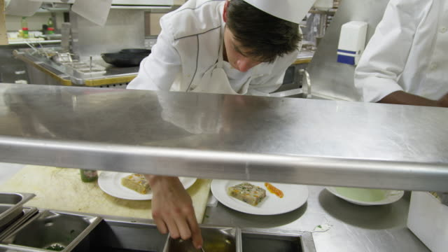 POV food being prepared at the plating area in a restaurant kitchen