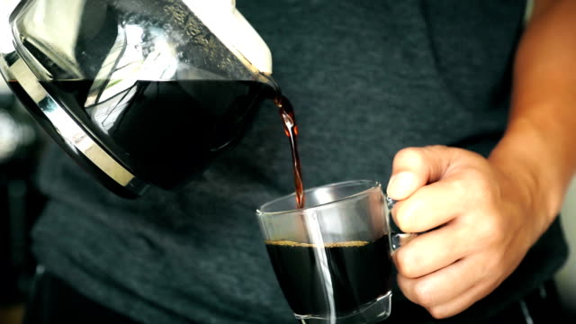 food cinemagraphs: a man pouring a mug of hot coffee from a glass pot in the morning at home. - mug stock videos and b-roll footage