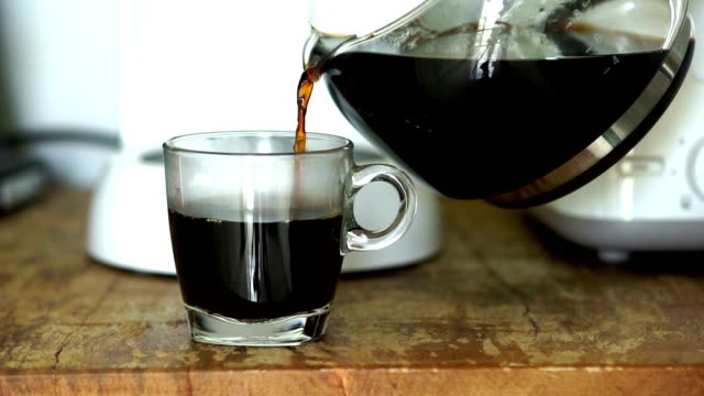 Food Cinemagraphs : Pouring a mug of hot coffee from a glass pot in the morning at home.