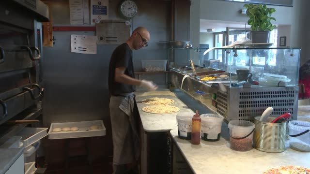 Food companies urged to take calories out of pizza to tackle obesity ENGLAND London INT Various of tomato sauce and cheese being spread onto pizza...