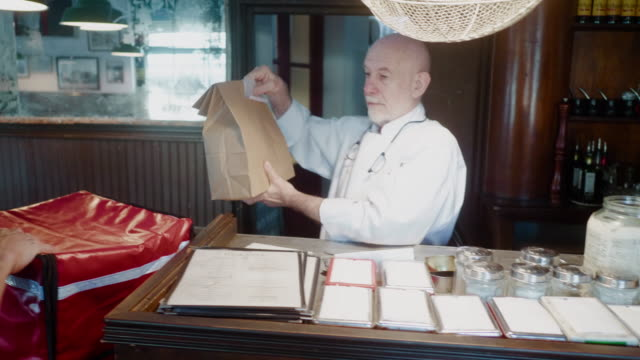 food courier getting his take away order from the restaurant - take away food stock videos & royalty-free footage