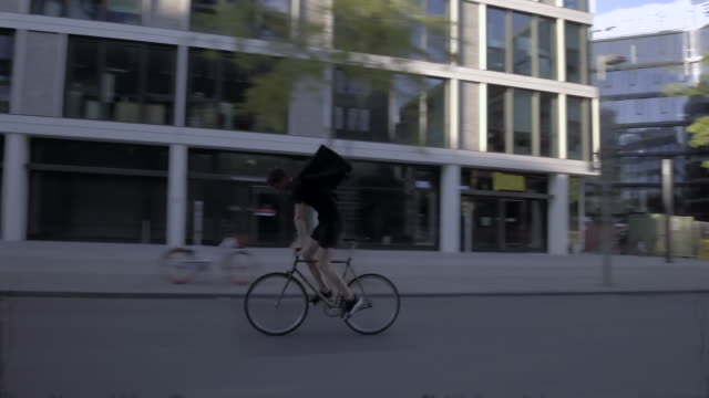food courier riding through business district - delivery person stock videos & royalty-free footage