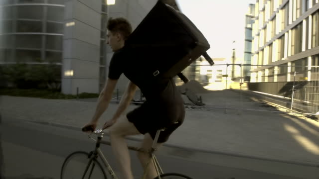 food courier riding through office district - take away food stock videos & royalty-free footage
