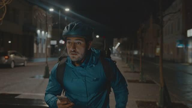 vídeos y material grabado en eventos de stock de repartidor de alimentos corriendo mientras busca dirección usando el teléfono móvil en la calle de la ciudad por la noche - chaqueta