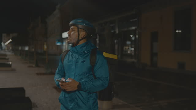 food delivery boy searching for address using mobile phone on city street at night - cycling helmet stock videos & royalty-free footage