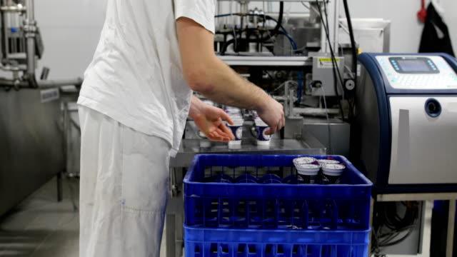 stockvideo's en b-roll-footage met voedsel fabriek. de werknemer verpakkingen plastic glazen yoghurt - dairy product