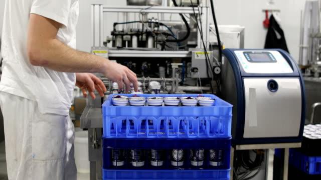 food factory.the worker packs plastic glasses of yogurt - belt stock videos & royalty-free footage