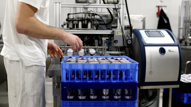 food factory.the worker packs plastic glasses of yogurt - crate stock videos & royalty-free footage