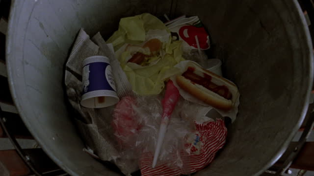 Food is thrown into a trash can.