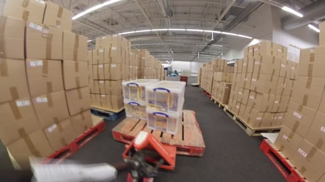 food poverty rising in london; england: london: ext go-pro point of view into curry's superstore int food stacked on pallets in makeshift warehouse... - warehouse点の映像素材/bロール