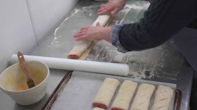 Food preparation in traditional UK Butchers shop making sausage rolls.