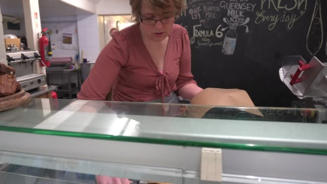 Food preparation in traditional UK Butchers shop serving customer.