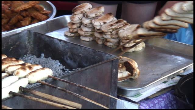 vídeos de stock, filmes e b-roll de (hd1080) preparação de alimentos: a banana grelhado e espetinhos de plntans de - banana de são tomé