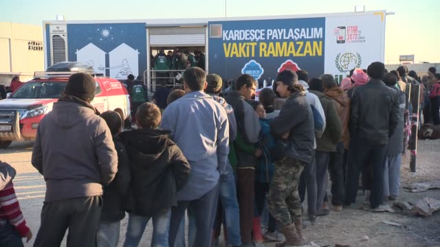 stockvideo's en b-roll-footage met food supplies are distributed by turkish ngo ihh humanitarian relief foundation to syrian refugees who have fled the attacks of syrian and russian... - in de rij staan