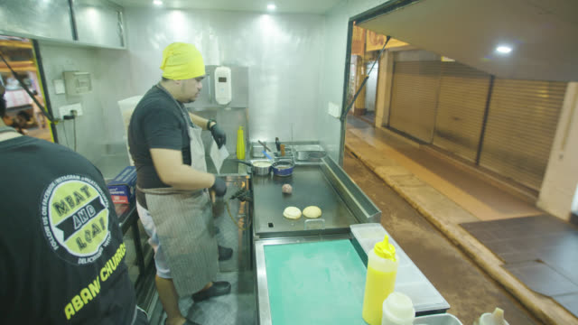 food truck chef grilling burger for cheeseburger in food truck - cheeseburger stock videos & royalty-free footage