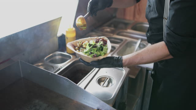 food truck owner plating up a dish - youth culture stock videos & royalty-free footage