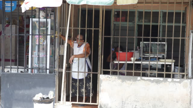 A food vendor leaning on the security bars of her shop in El Vertel a neighborhood with high criminality rate